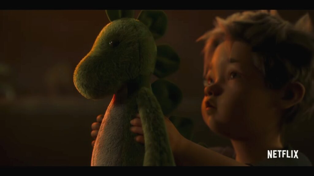 A small child offers his dinosaur plushie