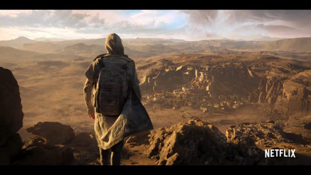 A hooded figure overlooks a desolate landscape