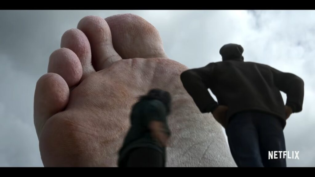 A massive foot dwarves two human onlookers